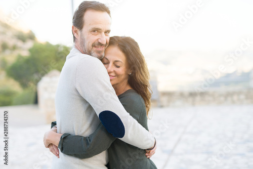 Fotografie, Obraz  Romantic couple smiling,  cuddling and hugging on a sunny day