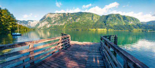 Old wooden pier on Bohinj lake. Colorful summer view of Triglav national park. Beautiful morning scene of  Slovenia, Alps, Europe. Beauty of nature concept background. Orton Effect.