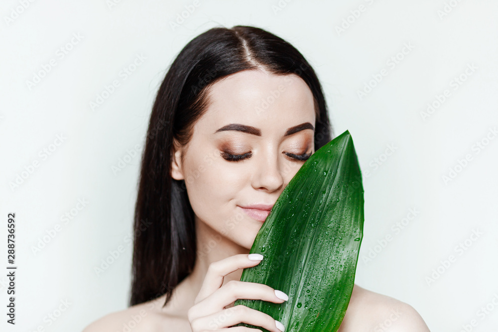 Fototapety, obrazy: Portrait of young beautiful woman with healthy glow perfect smooth skin holds green tropical leaf. Model with natural nude make up.