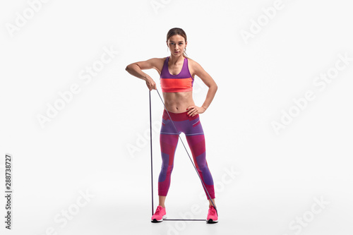 Fotografia Strong lady exercising with resistance band