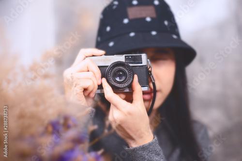 Fototapeta asian women take photo with vintage camera focus at camera obraz na płótnie