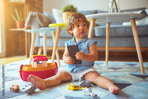 Fotografiet  Beautiful toddler child girl sitting on the carpet playing with smartphone