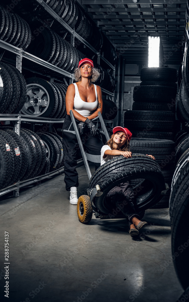 Fototapeta Strong female worker and her little helper have fun while looking for right tyres at warehouse.