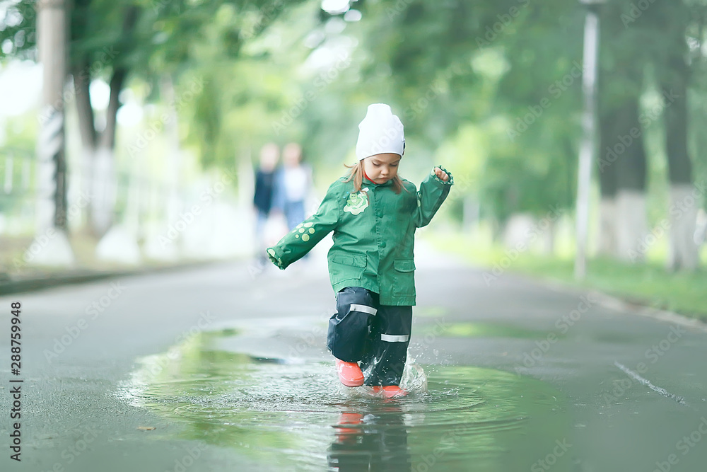 Fototapety, obrazy: cheerful little girl walks and jumps in puddles in the rain