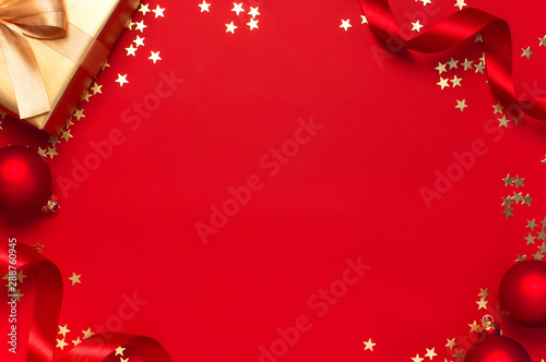 obraz dibond New Year Christmas golden presents with ribbon, Christmas balls, gold confetti stars on red background top view. Flat lay Xmas holiday 2020 celebration. Gift boxes greeting card Festive decorations