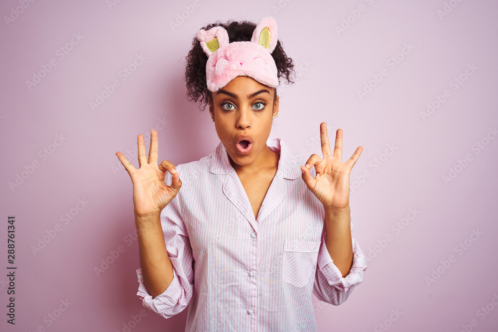 Fototapety, obrazy: Young african american woman wearing pajama and mask over isolated pink background looking surprised and shocked doing ok approval symbol with fingers. Crazy expression