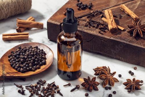 Obraz na plátně  Aromatic seeds essential oil on glass bottle