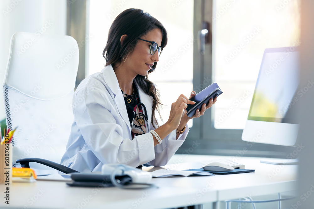 Fototapety, obrazy: Pretty young woman gynecologist using her mobile phone before starting consultation in the clinic.
