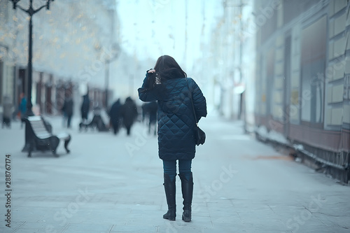 obraz PCV girl in a coat in the winter city / concept of fatigue stress christmas chores