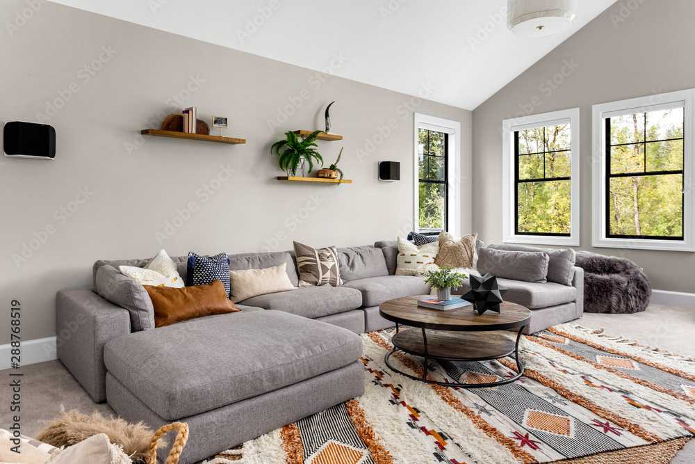 Fototapeta Beautiful living room in new luxury home. Features L shaped sectional sofa, area rug, and elegant decor