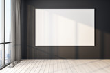 Fototapeta Kawa jest smaczna - Blank poster on black wall in modern empty room with big windows and wooden floor, mock up.