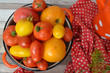 Russian cuisine: fresh ripe tomatoes in red casserole with dots pattern, top view