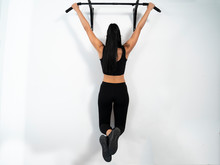 Female Hanging On Pull Ups Bar Indoors, White Wall