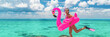 Happy fun beach vacation woman tourist ready to jump in ocean swimming with snorkel fins and pink flamingo toy pool float. Goofy swimmer girl running on holidays panoramic banner.
