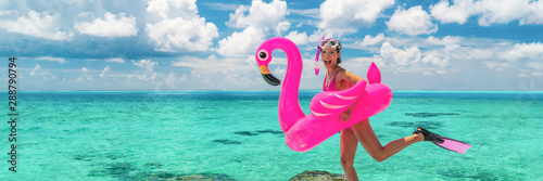 Photo  Happy fun beach vacation woman tourist ready to jump in ocean swimming with snorkel fins and pink flamingo toy pool float