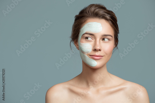 Portrait of beautiful woman with bluel cream mask on her face.