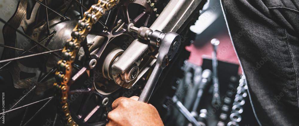 Fototapeta Mechanic working on motorcycle in garage. Repair service.