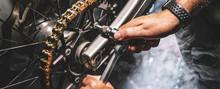 Mechanic Working On Motorcycle In Garage. Repair Service.