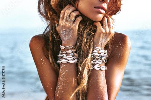 beautiful young stylish woman portrait on the beach at sunset