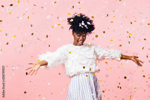Obraz Young woman smiling with arms open amid confetti falling - fototapety do salonu