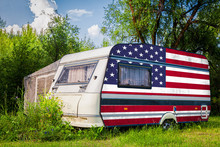 A Car Trailer, A Motor Home, Painted In The National Flag Of  USA Stands Parked In A Mountainous. The Concept Of Road Transport, Trade, Export And Import Between Countries.