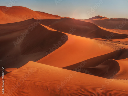 Sun rising over the red sand dunes of the Namib Desert, Namibia.