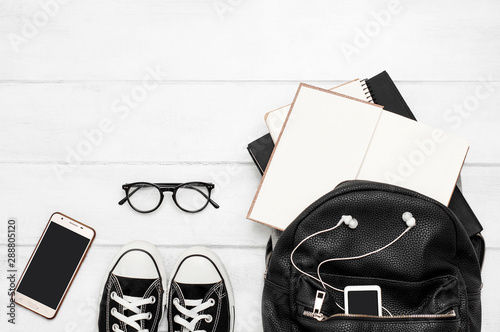 Obraz An open black backpack with books, a mobile phone, a player with headphones, glasses, notebook, gym shoes on a white wooden background. Back to school. Student. Top view. Flat lay - fototapety do salonu