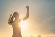 Leinwandbild Motiv Strong confident woman flexing arms facing the sunset.