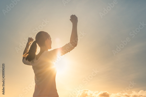 Fotografiet  Strong confident woman flexing arms facing the sunset.