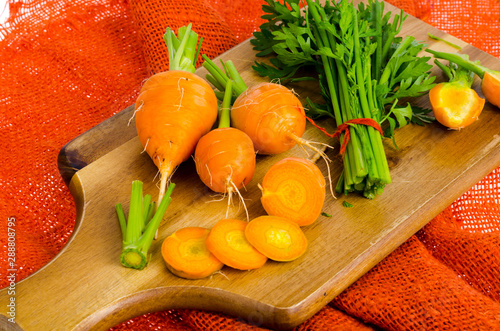 Bunch of small, round carrots (Parisian Heirloom Carrots) on wooden background. © ArtCookStudio