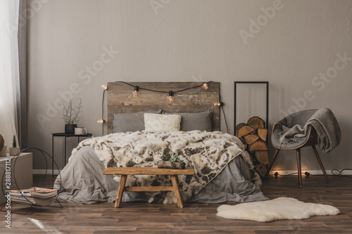 Photographie  Copy space on empty grey wall of stylish bedroom interior with wooden accents an