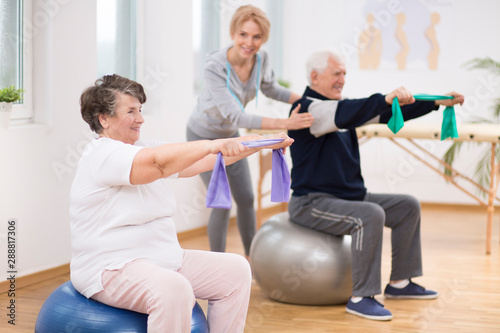 Tela Elderly man and woman exercising on gymnastic balls during physiotherapy session