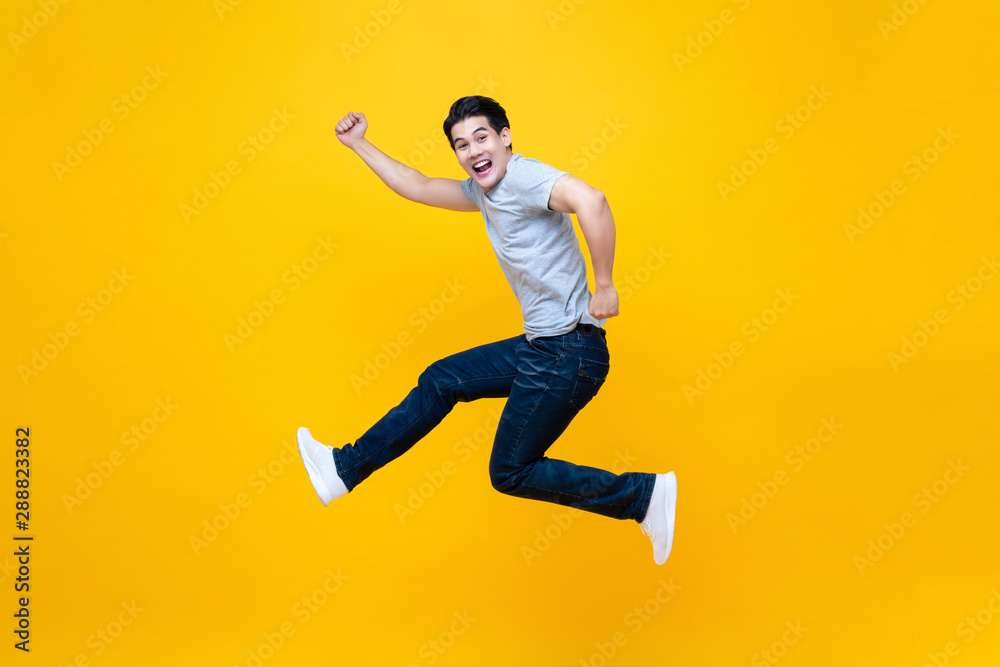 Fototapety, obrazy: Fun energetic young handsome Asian man jumping in mid-air