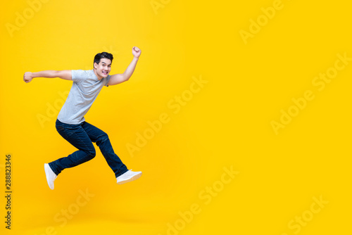 Fun energetic young handsome Asian man jumping in mid-air Canvas Print
