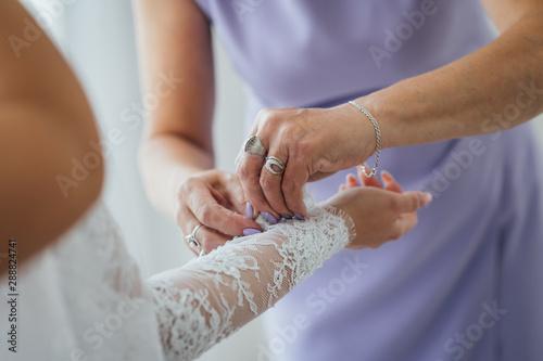 Bridesmaid preparing bride for the wedding day Canvas Print