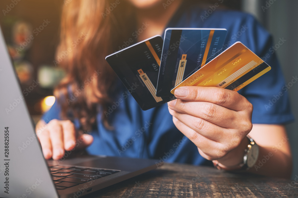 Fototapeta A woman holding credit cards while using laptop computer