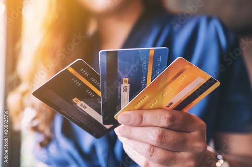 Valokuvatapetti Closeup image of a woman holding and showing credit card