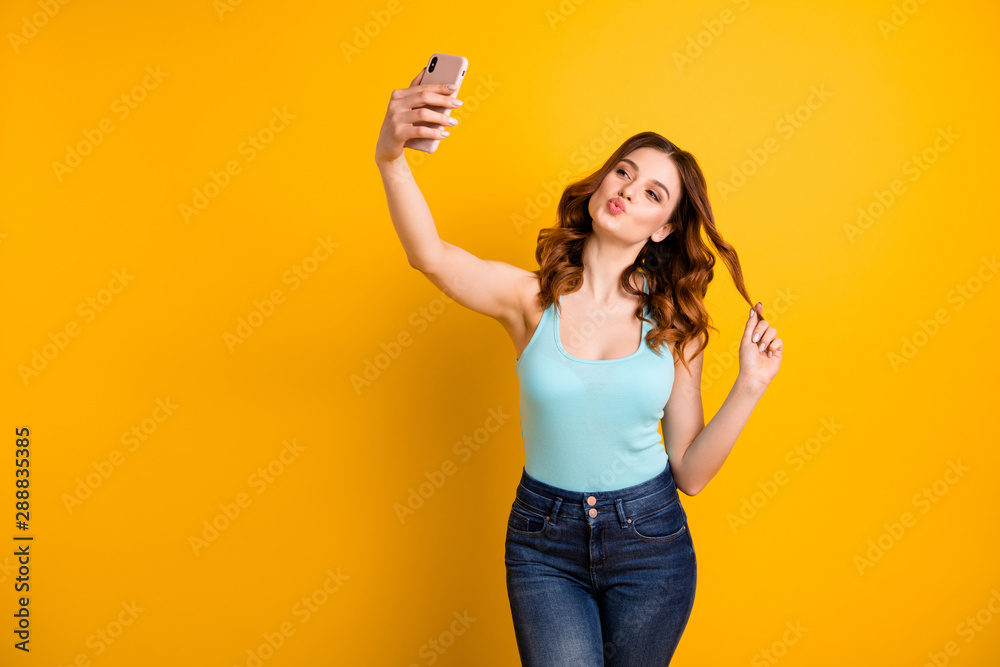 Fototapety, obrazy: Photo of lady holding telephone making self photos with coquette kisses wear tank-top and jeans isolated yellow background