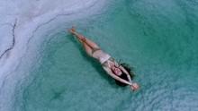 Beautiful Girl Floating In The Dead Sea Salt