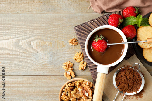 Obraz na plátně  Dipping strawberry into fondue pot with milk chocolate on wooden table, flat lay