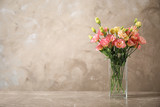 Eustoma flowers in vase on table near beige wall, space for text