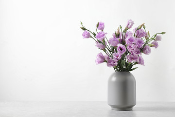 Eustoma flowers in vase on table near white wall, space for text