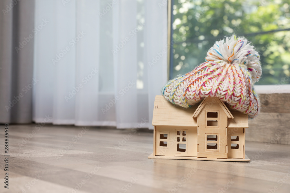 Fototapeta Wooden house model in hat on floor indoors, space for text. Heating efficiency