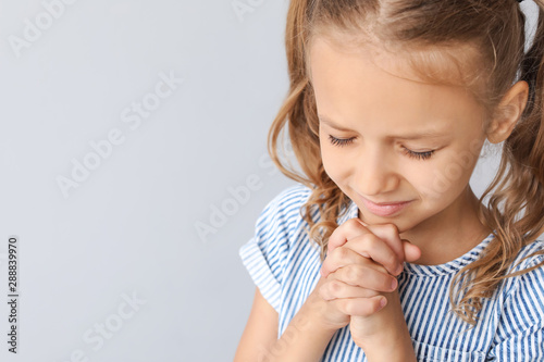 Photo Praying little girl on light background