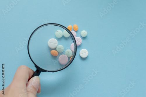 Magnifying glass with pills on blue background Billede på lærred