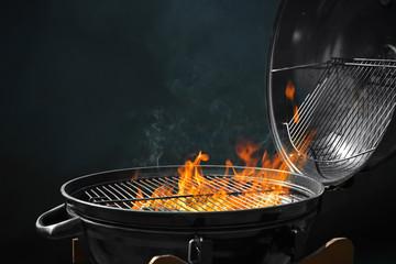 Suvremeni roštilj s gorućom vatrom na tamnoj pozadini