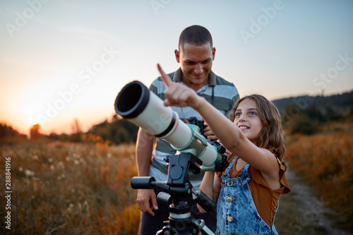 Father and daughter observing the sky with a telescope. - 288841916