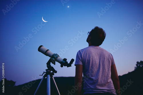 Astronomer with a telescope watching at the stars and Moon Canvas Print