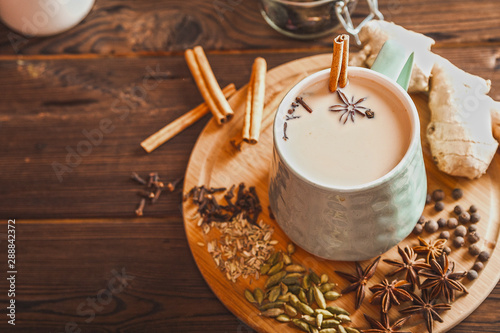 Details of still life in the home interior living room. Beautiful Cup of tea with milk, star anise, cinnamon on a wooden background. Cozy autumn-winter concept. Masala is a traditional hot spicy drink