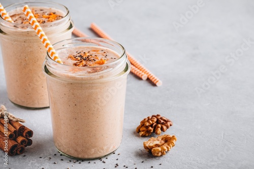 Obraz na plátně Healthy carrot and apple smoothie with walnuts and chia seeds in glass jars